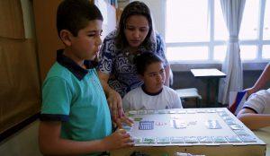 Carlos manuseia Jogo da Trilha Interativo auxiliado pela professora Karina. Fim da descrição