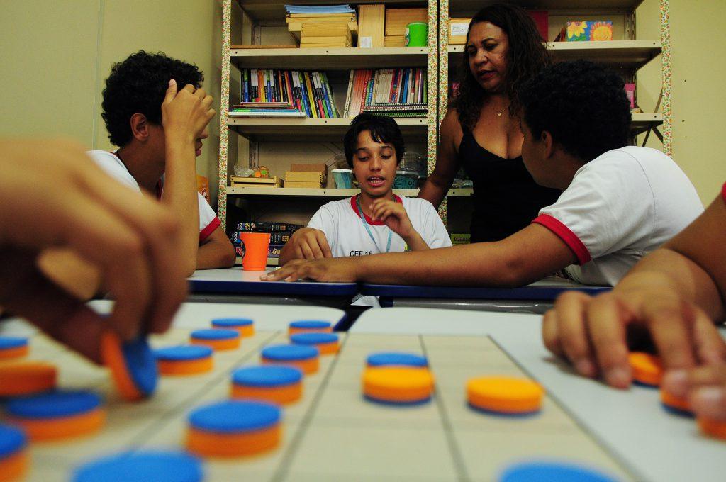 Em sala de recursos multifuncionais, alunos conversam observados por professora.