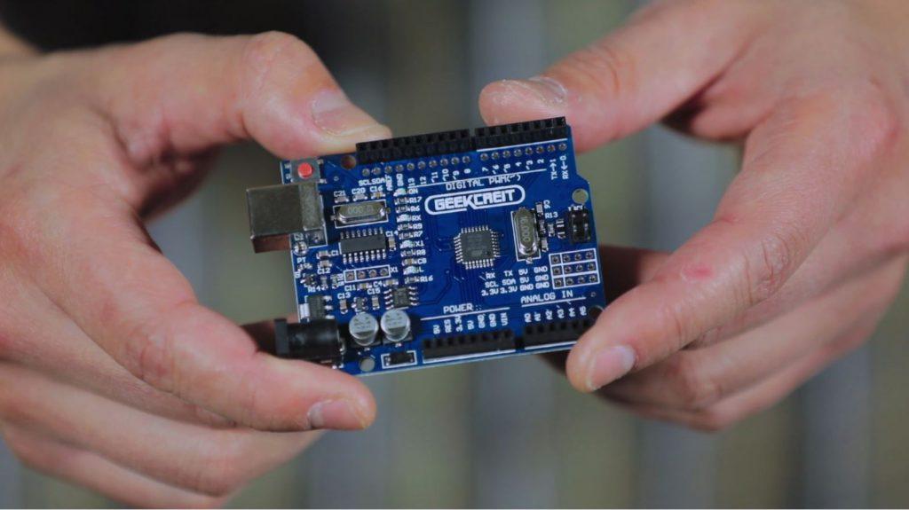 Pessoa exibe um arduino, que é uma placa azul retangular com vários conectores. Fim da descrição
