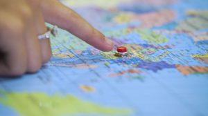 Pessoa aponta com o dedo indicador botão localizado em região continental do Mapa mundi interativo. Fim da descrição,