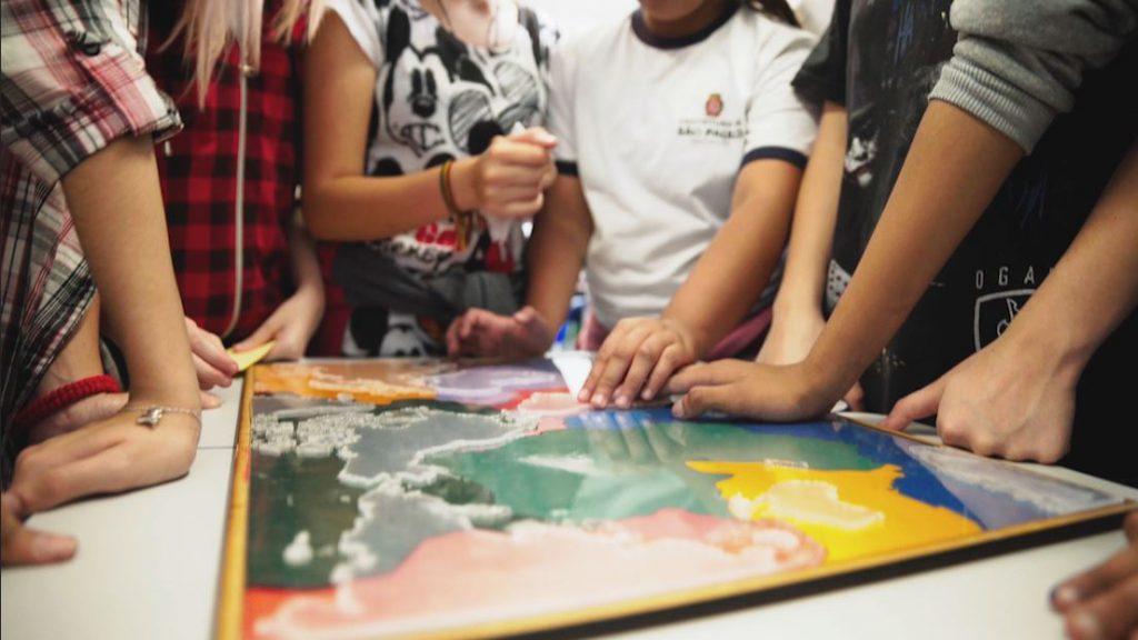 Estudantes manuseiam o material pedagógico acessível Placas Tectônicas. Fim da descrição.