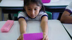 Aluna em sala de aula segura e olha cartão roxo com os braços sobre a mesa. Fim da descrição.
