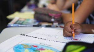 Imagem de caderno em que estudante pinta desenho do mapa mundi. Fim da descrição.
