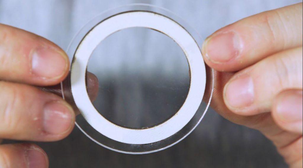 Pessoa exibe auréola colada a um acrílico transparente. Fim da descrição.