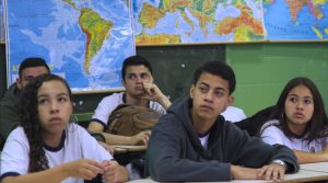 Cinco estudantes concentrados sentados em cadeiras em sala de aula Fim da descrição
