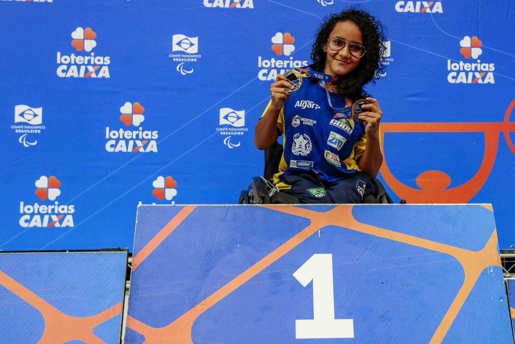 A atleta Lara posa com suas medalhas no primeiro lugar do pódio do Circuito Loterias Caixa 2019. Fim da descrição.