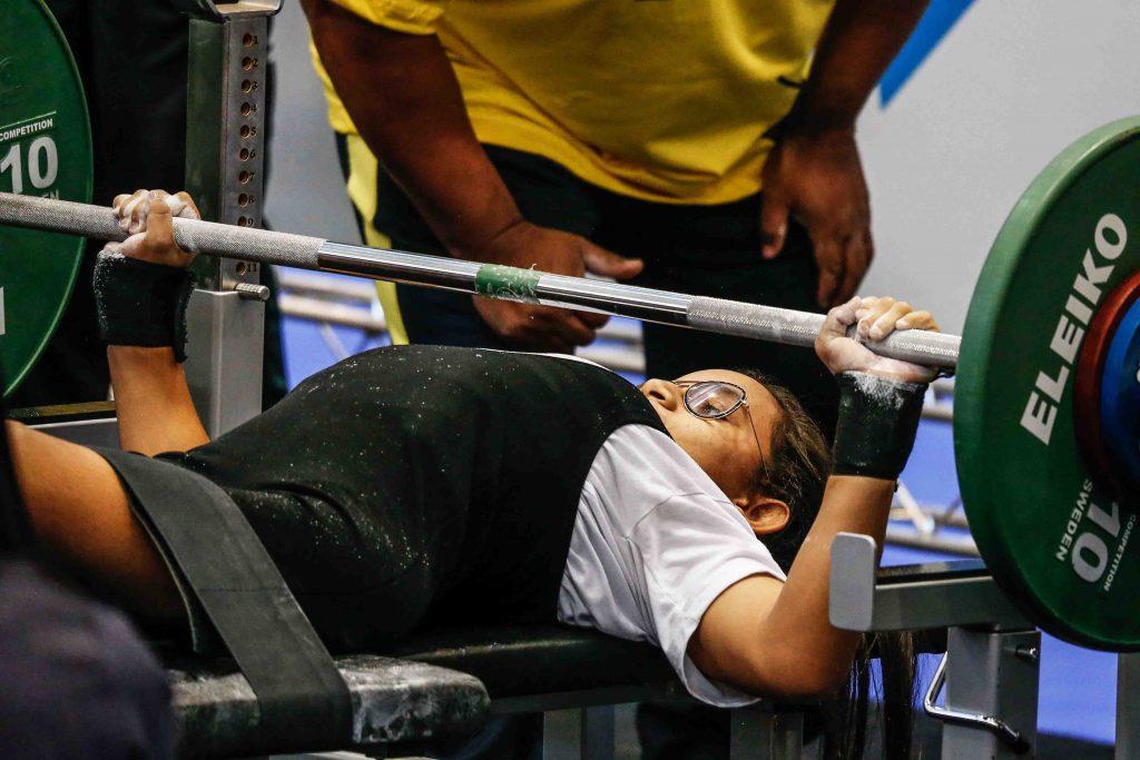 Atleta Lara Aparecida em treinamento de halterofilismo. Deitada em uma esteira, ela levanta uma barra de aço com pesos em suas extremidades, com o professor ao seu lado. Fim da descrição.