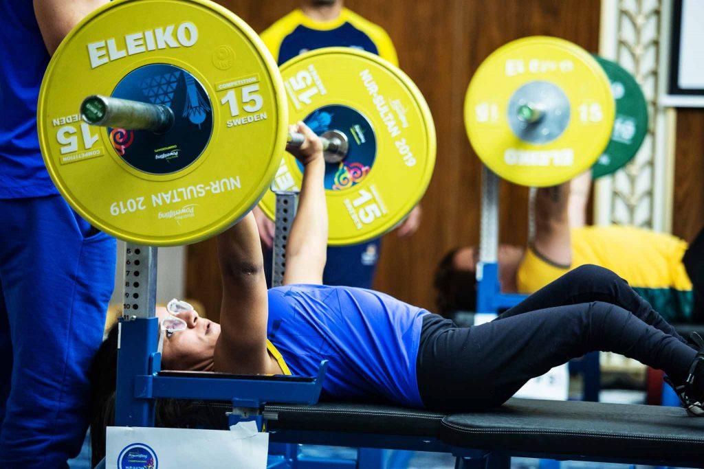 Atleta Lara Aparecida em treinamento de halterofilismo. Deitada em uma esteira, ela levanta uma barra de aço com pesos em suas extremidades. Fim da descrição.