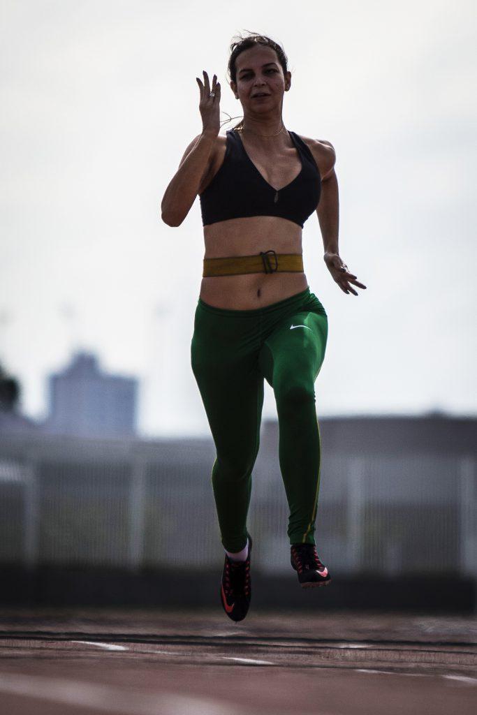 Atleta Lorena Spoladore treina corrida em pista. Fim da descrição.