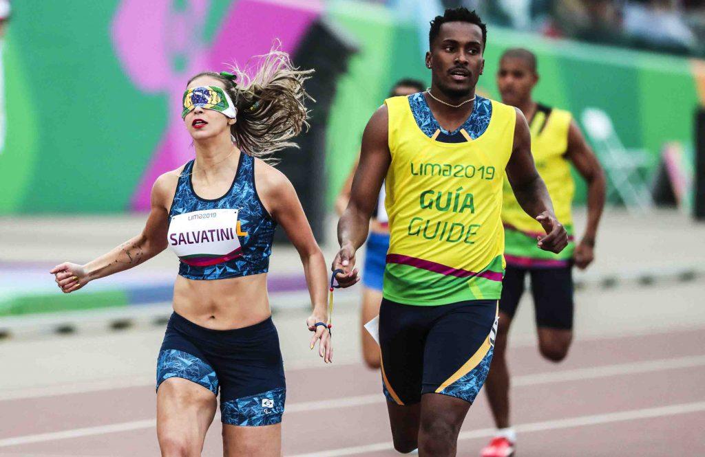 Atleta Lorena Spoladore e seu guia correm na pista dos Jogos Parapanamericanos Lima 2019. A atleta usa uma proteção nos olhos. Fim da descrição.