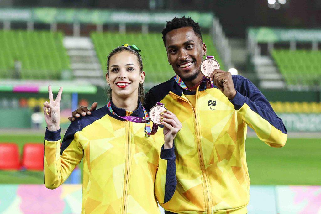 A atleta Lorena Spoladore e seu guia posam com suas medalhas nos Jogos Parapanamericanos Lima 2019. Fim da descrição.