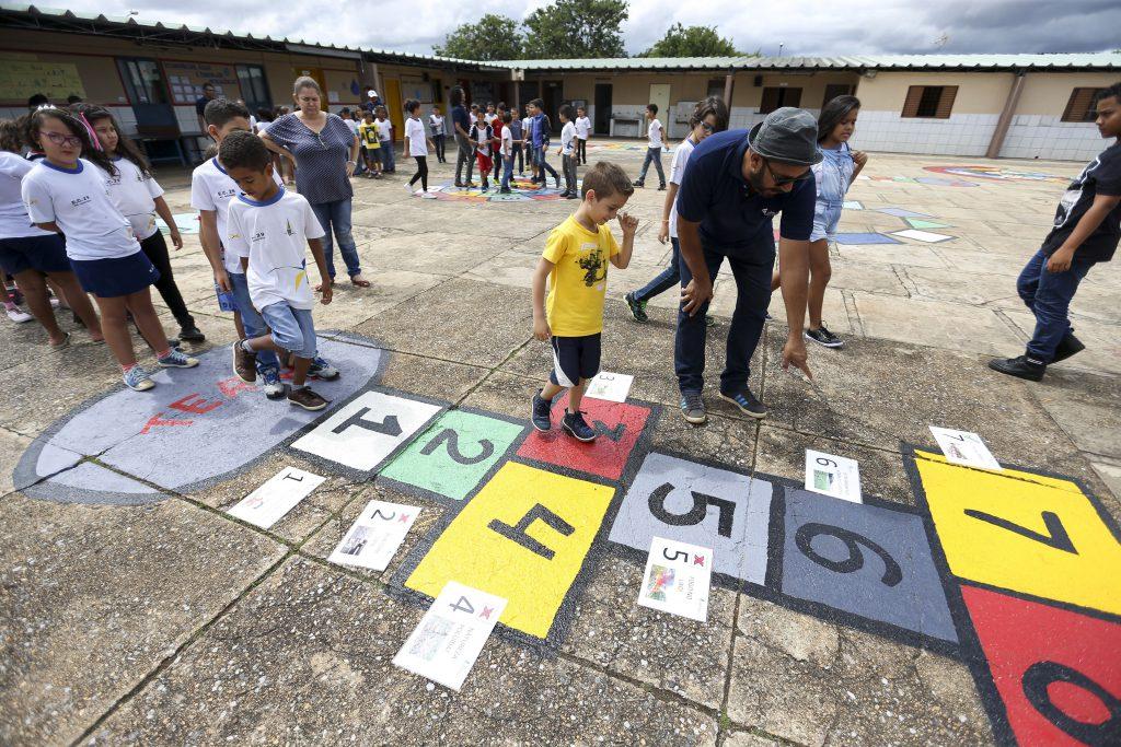 """Imagem de crianças jogando """"amarelinha"""" em pátio de escola. Menino de camisa amarela anda sobre o número """"3"""" do jogo, sendo orientado por professor levemente curvado aponta para o número """"6"""". Outras crianças esperam a sua vez na posição """"Terra"""" do jogo, localizada à esquerda da foto. Fim da descrição."""