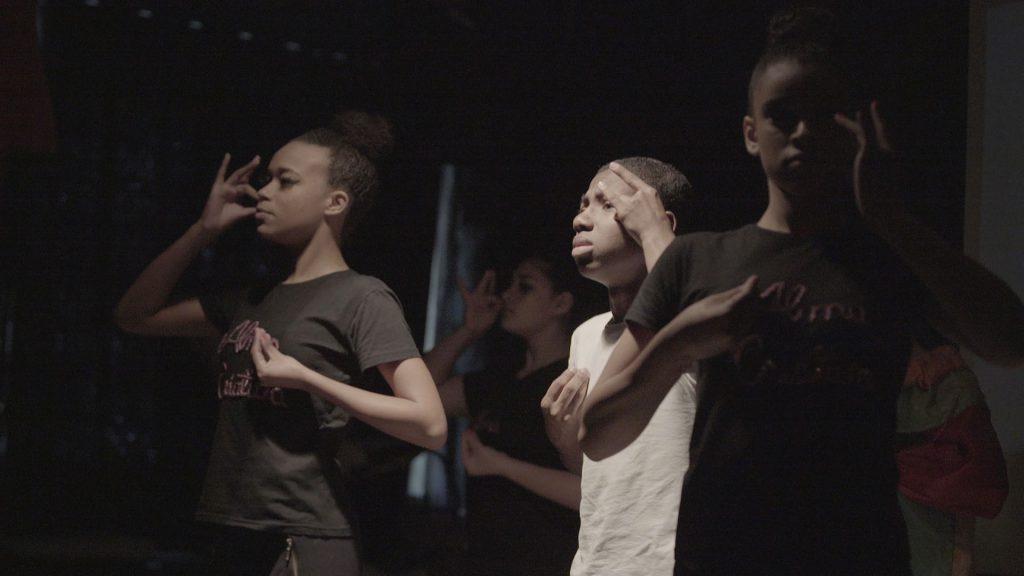 Quatro estudantes encenam musical inclusivo. Eles olham pra frente e fazem uso de Libras. Fim da descrição.