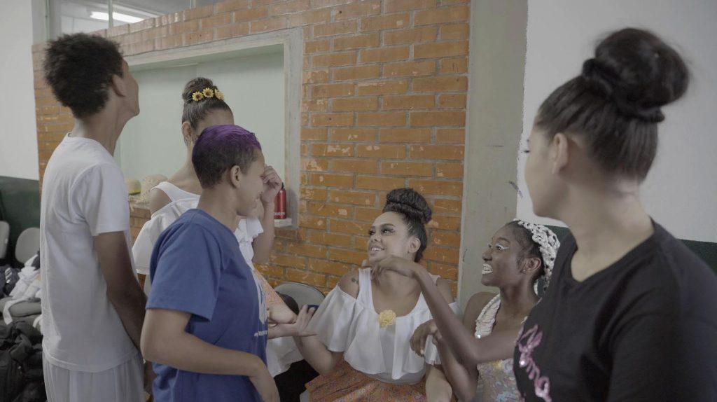 Seis estudantes vestidos para a peça do musical inclusivo conversam em Libras no camarim. Fim da descrição.