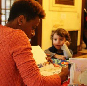 Janine folheia livro. Em sua frente, uma criança a observa. Fim da descrição.