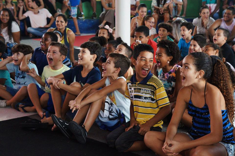 Grupo de crianças sentadas no chão demonstra empolgação ao ouvir história. Fim da descrição.
