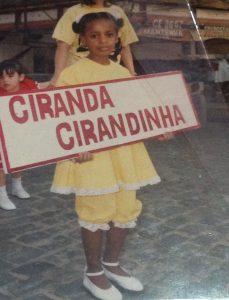 """Janine criança com fantasia caipira amarela posa para foto segurando placa com o texto """"Ciranda Cirandinha"""". Fim da descrição."""
