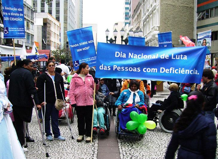 """Grupo de pessoas com deficiência realiza passeata em rua de Curitiba em 2008. Duas pessoas seguram um cartaz azul com o seguinte texto: """"Dia Nacional de Luta das Pessoas com Deficiência"""". Fim da descrição."""