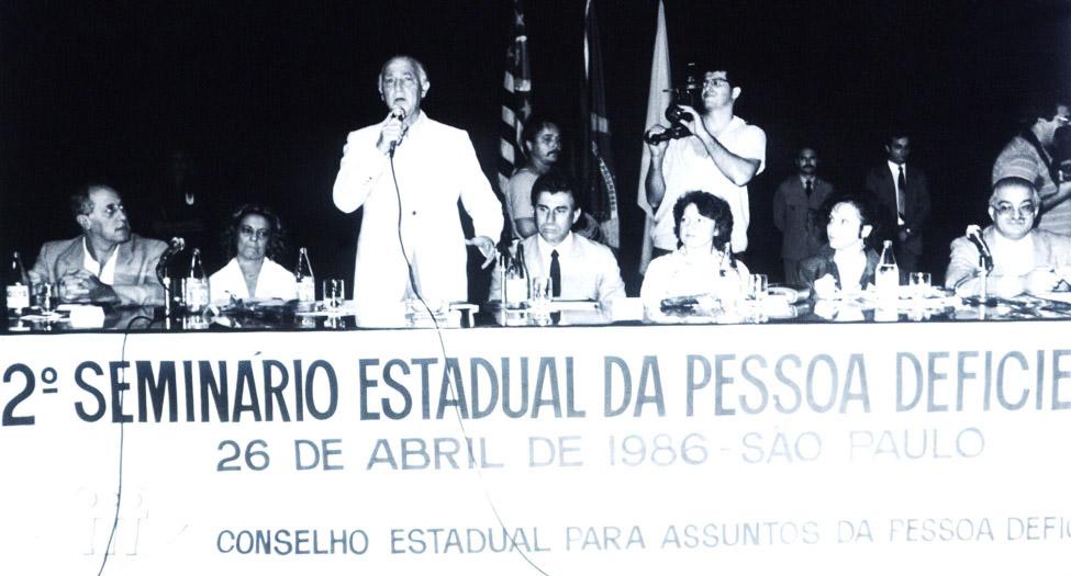 """Pessoas reunidas em volta de uma mesa de debates participam do """"2º Seminário Estadual da Pessoa Deficiente"""", realizado em 1986. Um senhor em pé discursa com microfone. Fim da descrição"""