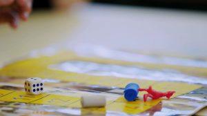 Imagem do tabuleiro da Trilha dos seres Vivos. Sobre o tabuleiro, há um dado, uma miniatura vermelha de um suricato e dois pinos (um branco e um azul). Fim da descrição.