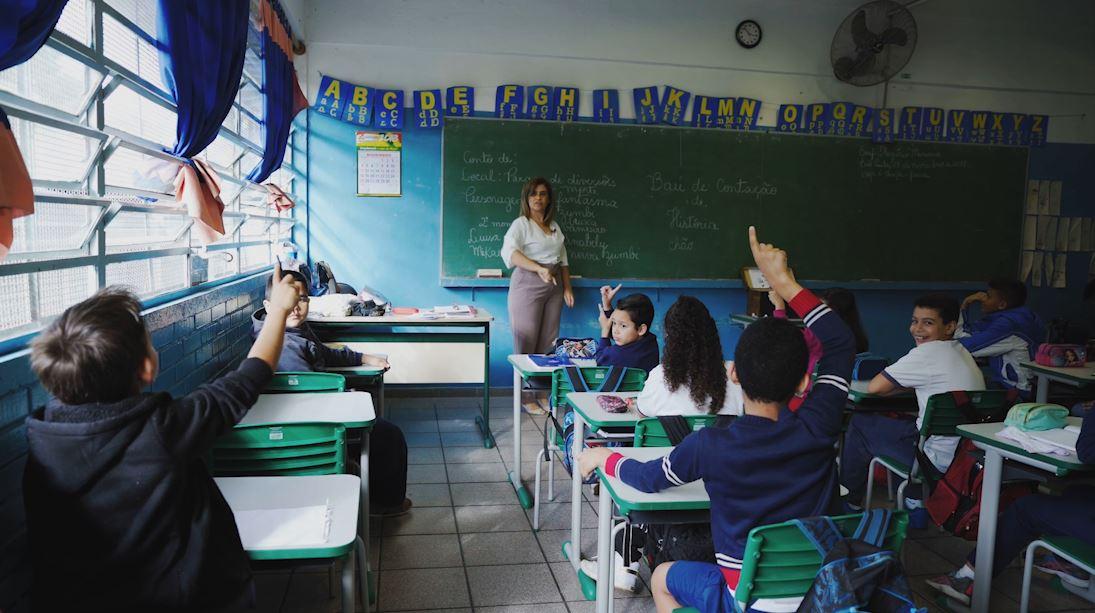 Em sala de aula, estudantes estão de costas sentados nas carteiras. Dois deles levantam enquanto professora os observa em pé à frente da lousa. Fim da descrição.