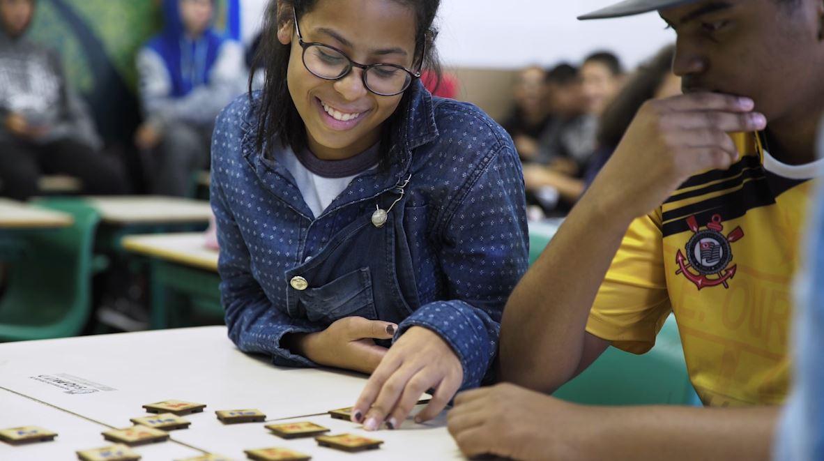 Em sala de aula, aluna sorridente e debruçada sobre mesa movimenta uma das peças do jogo da tabela periódica magnética. Ao lado dela, sentado e com os braços sobre a mesa, colega a observa. Fim da descrição.
