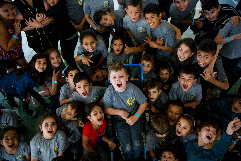 Imagem aérea de grupo de estudantes abraçados posando para câmera. Ao centro, estudante com deficiência sentado em cadeira de rodas. Fim da descrição.