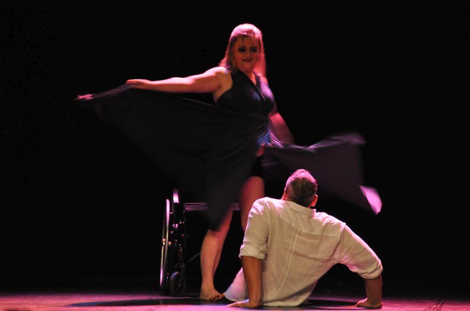 Fernando Passos sentado no palco e de costas para a plateia observa movimento de bailarina. Fim da descrição