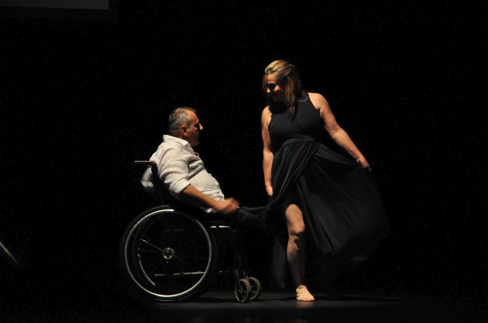 Fernando Passos dança sobre cadeira de rodas ao lado de dançarina. Fim da descrição.