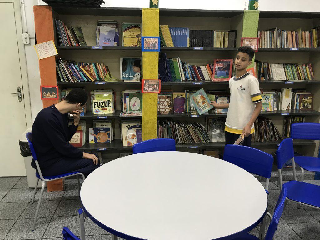 Nathan e Jonathan escolhem livros em frente à uma das estantes. Nathan está sentado à esquerda, enquanto Jonathan, à direita, está de pé. Fim da descrição.