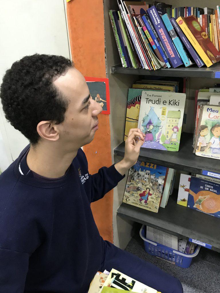 Nathan sentado e de frente para a estante segura um dos livros da estante com a mão esquerda. Fim da descrição.