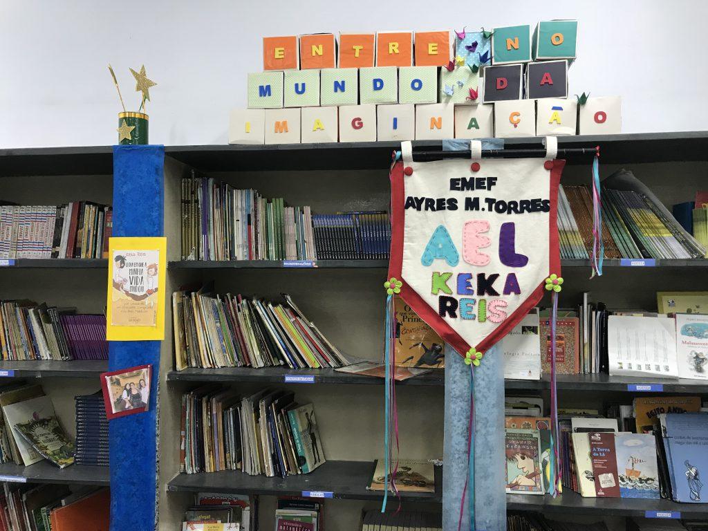 """Estante com livros em sala de leitura da EMEF Ayres Martins Torres. Acima da estante, a seguinte frase está escrita em três fileiras de cubos de papel: """"entre no mundo da imaginação"""". Abaixo dos cubos e em viga de sustentação à direita, brasão da escola. Fim da descrição."""