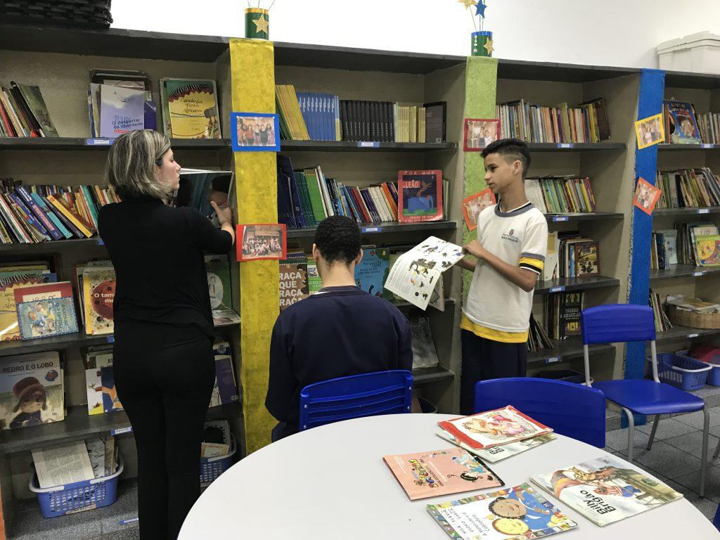Amanda de pé em frente à estante de livros, Amanda auxilia alunos a selecionarem estudantes para a contação de histórias. Nathan está no centro sentado em cadeira e de frente para a estante. Jonathan está em pé à direita e folheia um livro. Fim da descrição.