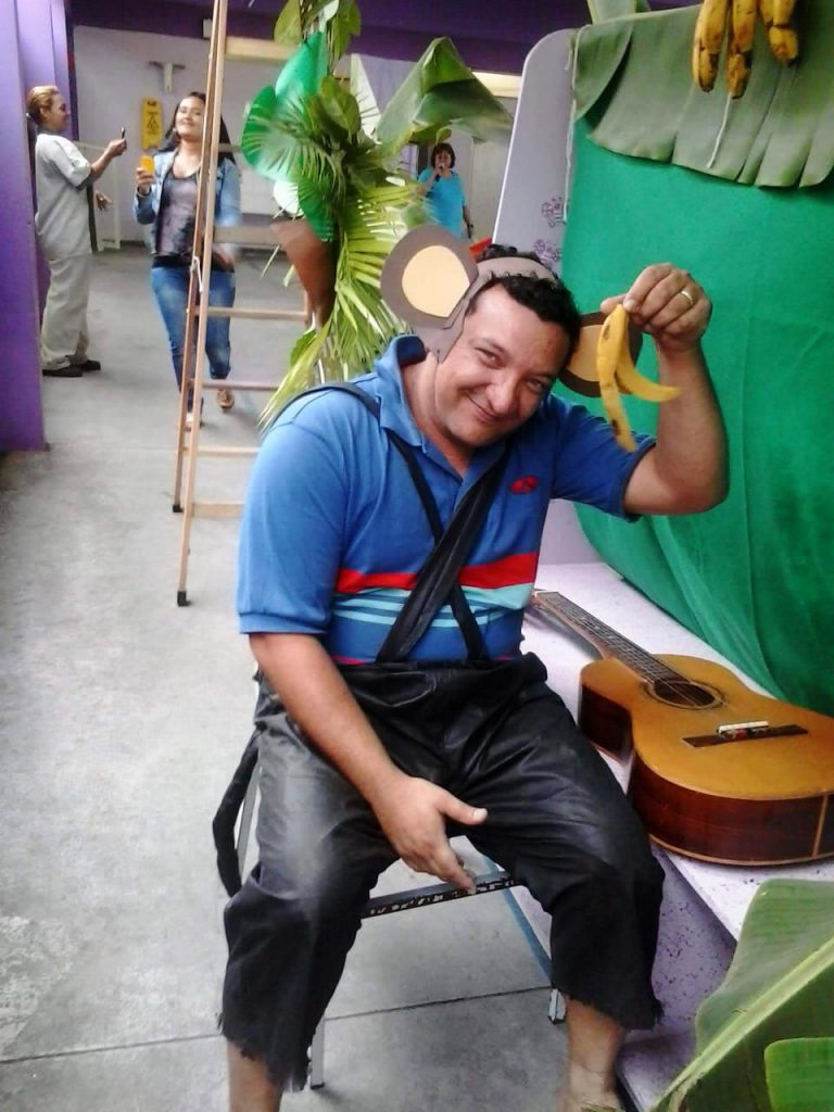 Samuel posa pra foto sentado em cadeira com fantasia de macaco e segurando uma casca de banana. Ao seu lado, depositado sobre um banco, está um violão. Fim da descrição.
