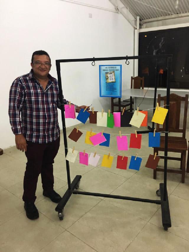 Samuel posa para foto ao lado de painel com papeis coloridos contendo cordéis, pendurados em um varal. Fim da descrição.