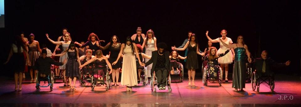 Grupo de dançarinos realiza apresentação artística em palco. Estão de mãos dadas. Entre eles, cadeirantes e pessoas sem deficiência. Fim da descrição.