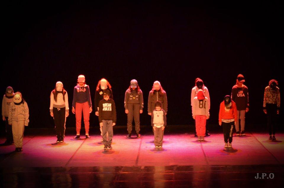 Grupo de crianças em pé realiza apresentação artística em palco. Fim da descrição.