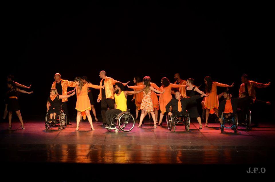 Em palco, grupo de pessoas com e sem deficiência faz passo de música com um dos braços esticado para a direita e a cabeça virada para a esquerda. Há pessoas em cadeiras de rodas e outras em pé.