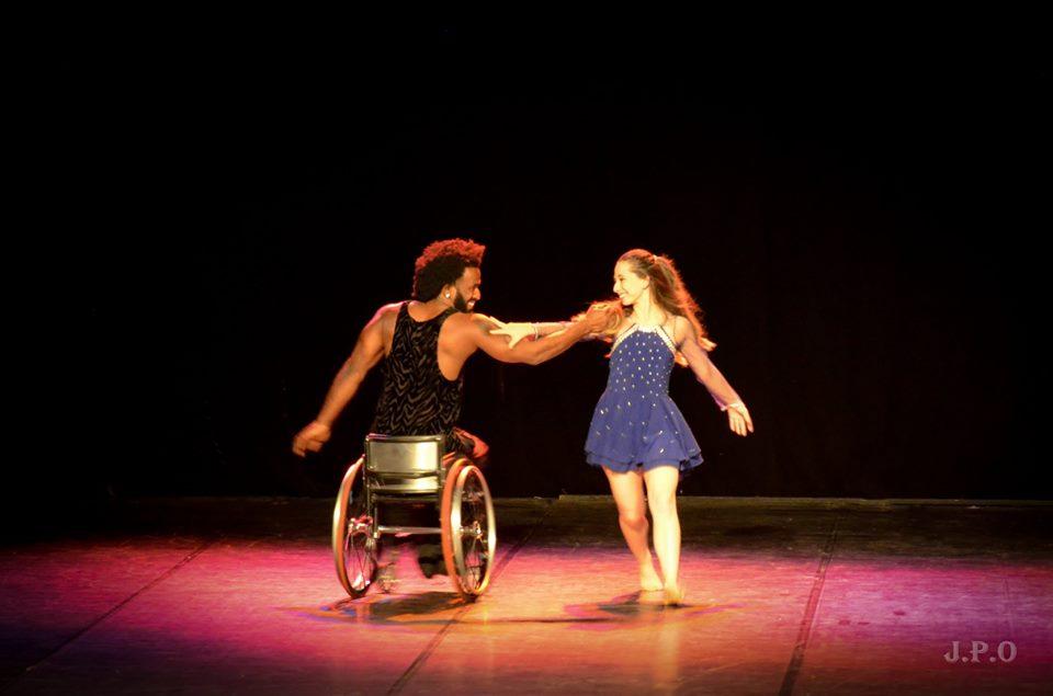 Dançarino sobre cadeira de rodas segura braço de bailarina em pé. Fim da descrição.