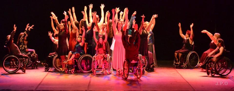 Grupo de dançarinos realiza apresentação artística em palco levantando as mãos. No grupo, há cadeirantes e pessoas sem deficiência. Fim da descrição.