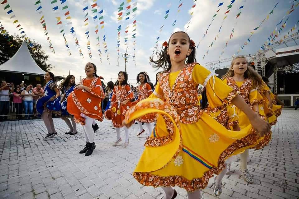 Estudantes caracterizadas com roupas juninas dançam quadrilha em praça. Acima delas, diversas bandeirinhas de festa junina decoram o espaço. Fim da descrição.