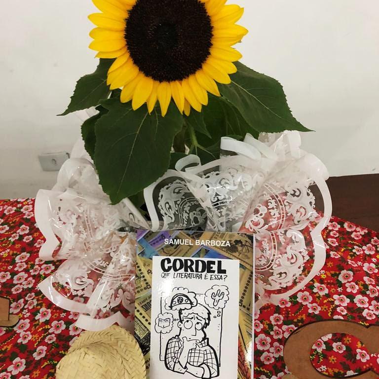 """Livro de Samuel Barboza, """"Cordel: que literatura é essa?"""" apoiado em um girassol sobre uma mesa com toalha decorativa floral vermelha. Ao lado, há um chapéu caipira de palha. A ilustração de capa do livro é um homem com três balões de pensamento: um com um livro, outro com chapéu de cangaceiro, e outro com um cacto. Fim da descrição."""