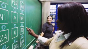"""Estudante, observada por professora, aponta para sílabas escritas na lousa. Escritas na lousa estão as sílabas e letras """"per"""", """"ão"""", """"ni"""", """"a"""", """"de"""", """"za"""", """"u"""", """"to"""", """"res"""" e """"gra"""". Fim da descrição."""