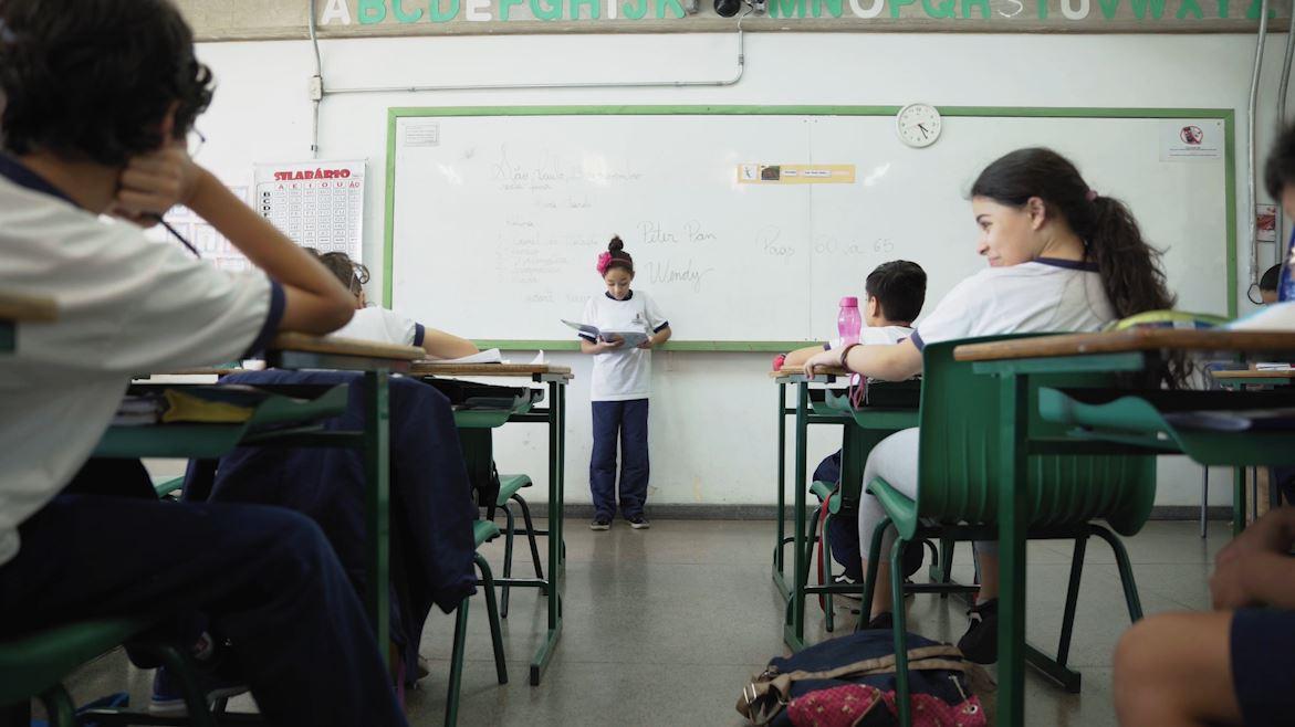 Em sala de aula, aluna em pé e de costas para a lousa lê livro apoiado em suas mãos, enquanto os demais alunos a observam sentados nas carteiras. Fim da descrição.