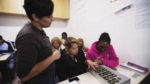 Duas alunas sentadas em carteiras escolares interagem com material pedagógico acessível Caixa silábica enquanto professora, de pé, as observa. Fim da descrição.