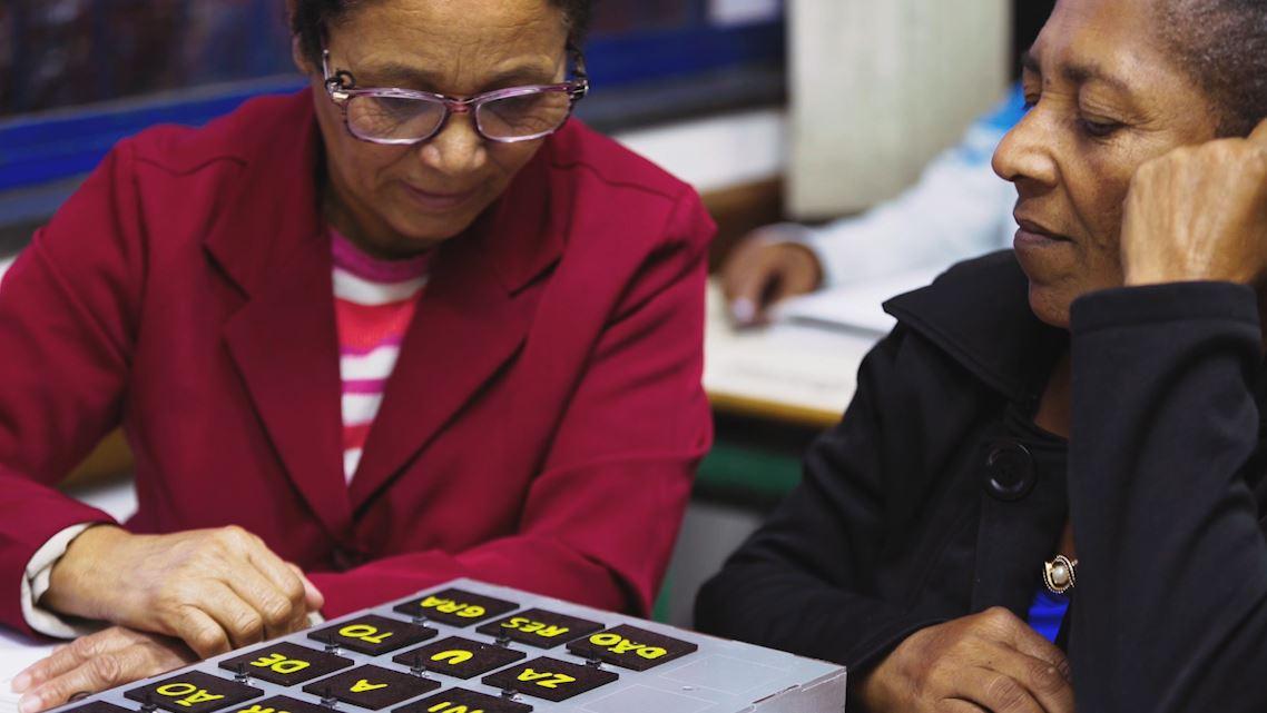 Duas senhoras negras sentadas em carteiras escolares interagem com o material pedagógico acessível Caixa silábica. Fim da descrição.