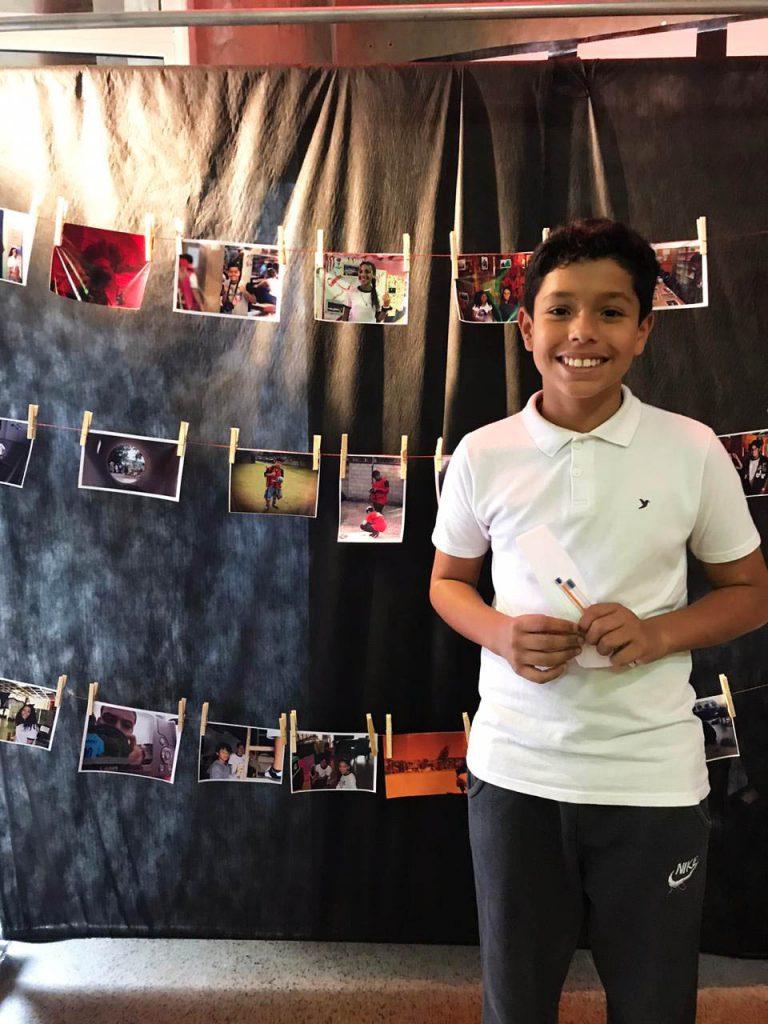Ezequiel Feliciano posa para foto sorridente segurando duas canetas e folhas de papel entre as mãos. Ao fundo, fotografias estão penduradas em varais em frente a um fundo preto. Fim da descrição.