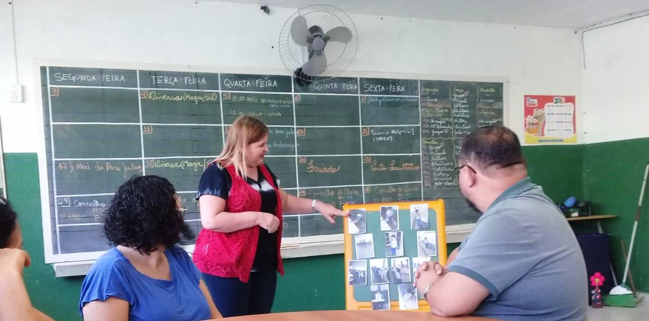 Em sala de aula, educadora aponta para painel com fotos de Pedro observada por três pessoas sentadas ao redor de uma mesa. Ao fundo, lousa escolar com calendário das atividades da semana. Fim da descrição.