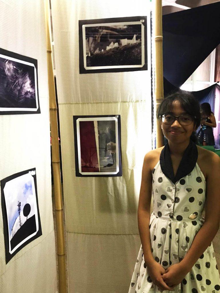 Sara Brandão posa para foto de pé ao lado de estande de fotografias. Fim da descrição.
