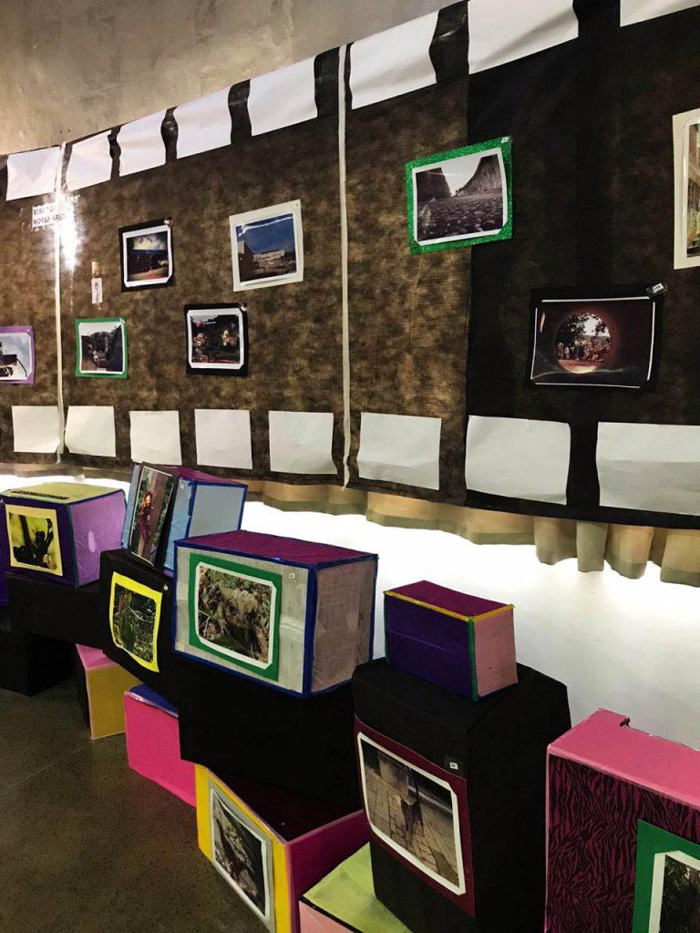 Imagem de cobertura da exposição. Na parede, tecidos de TNT estão colados de forma a simular um rolo fotográfico. No tecido, estão coladas algumas fotografias. No chão, caixas de papelão cobertas com tecidos coloridos estão empilhadas organizadamente, e cada caixa tem uma fotografia colada. Fim da descrição.